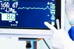 Female doctor pointing to Heart rate monitor in operation room.Healthcare and Medical concept. Hospital and People theme.